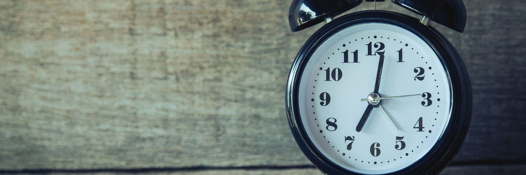 Alarm clock against wooden background