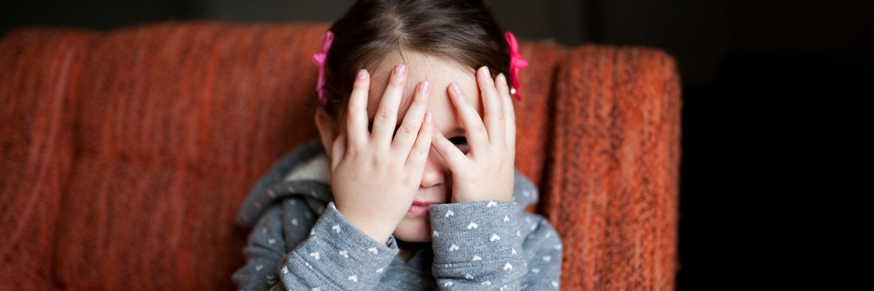 Embarrassed young girl hiding her eyes