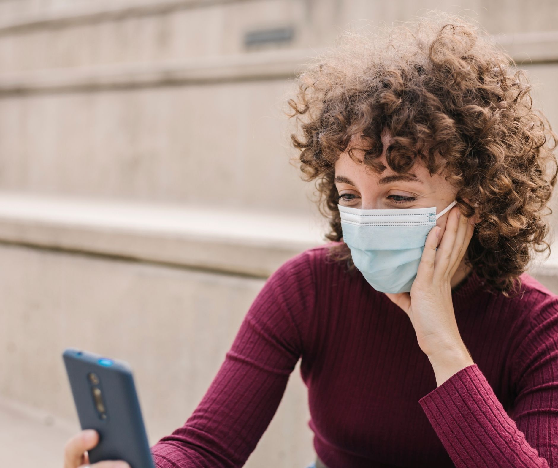Woman looking at phone and wearing mask