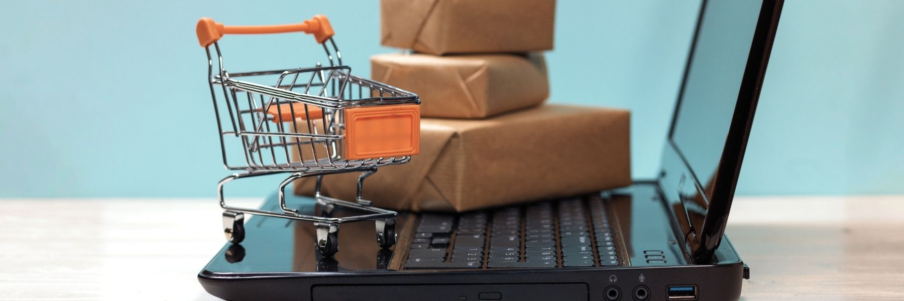 Tiny shopping cart and wrapped packages balanced on a laptop