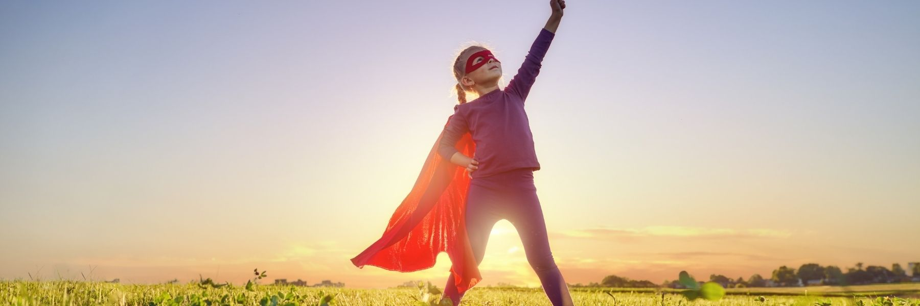 Young girl in a superhero outfit in front of sun