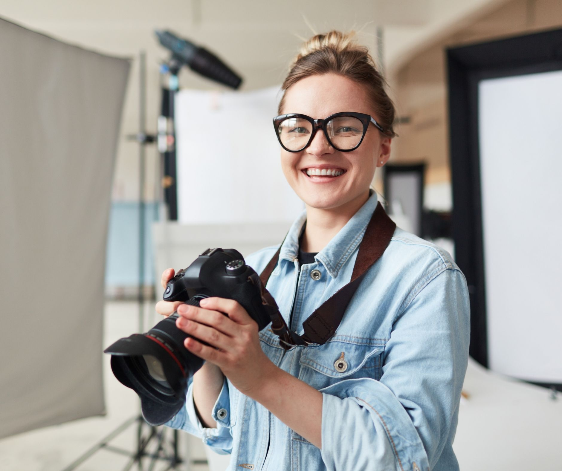 Woman holding professional camera and smiling.
