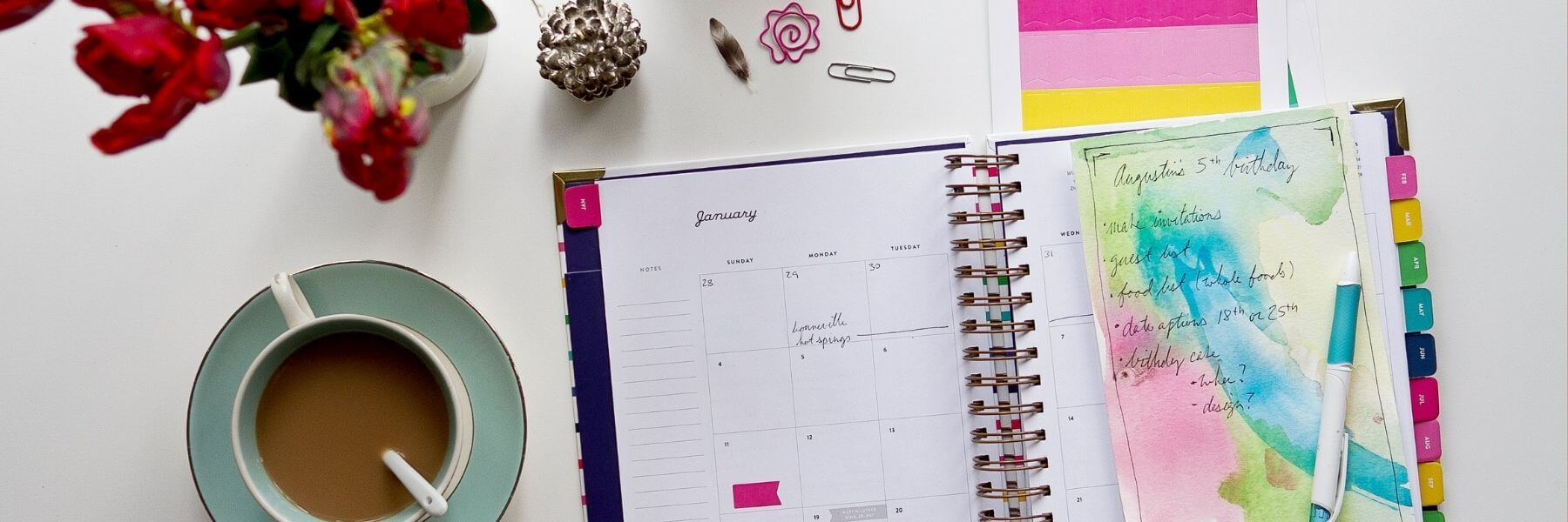 Desktop with flowers, planner, and organization.