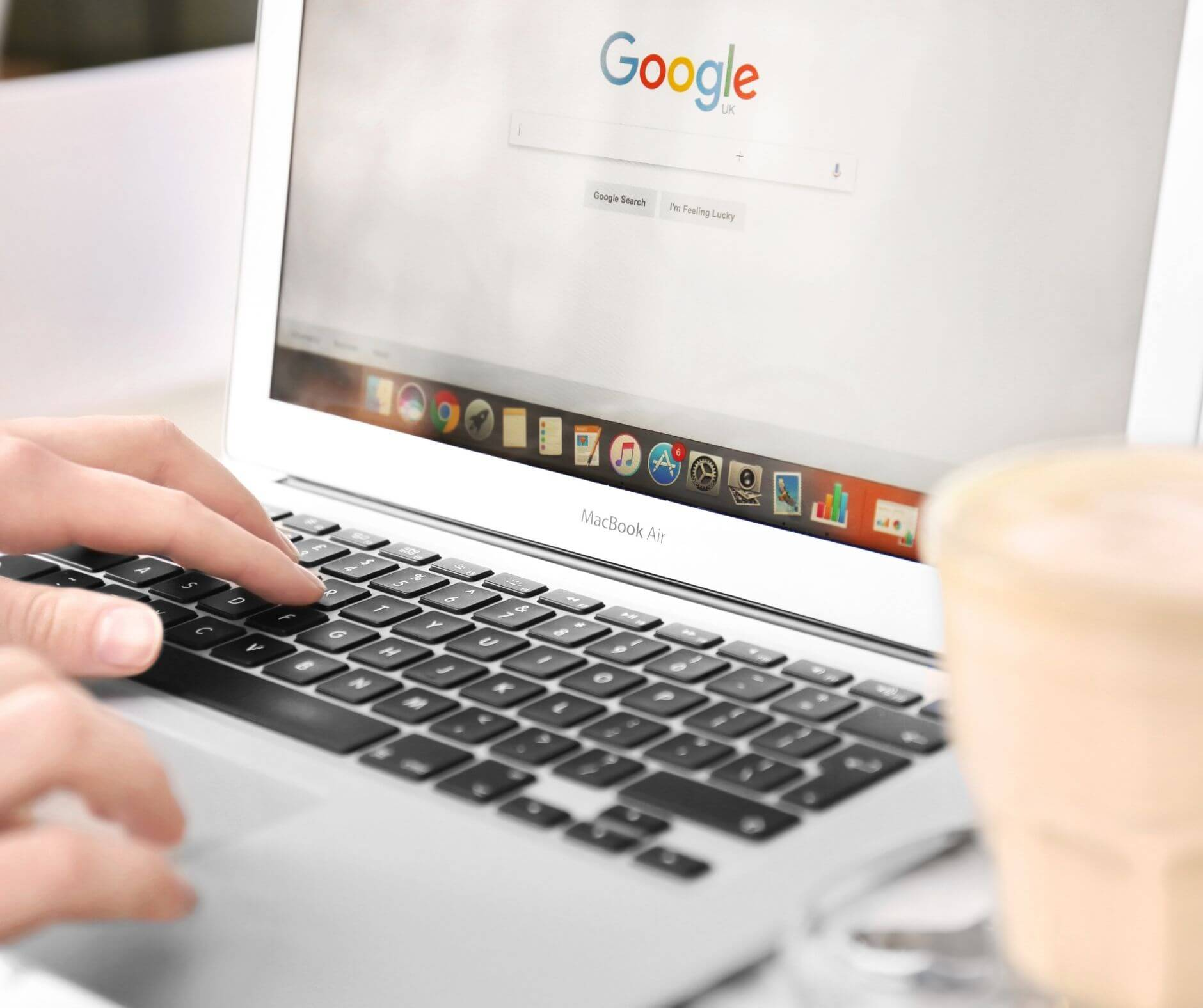 Person typing on laptop with Google showing in browser.